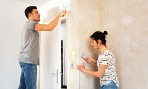 Paar streicht Wand weiß