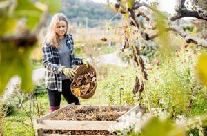 Junge Frau sammelt Laub in wildem Garten