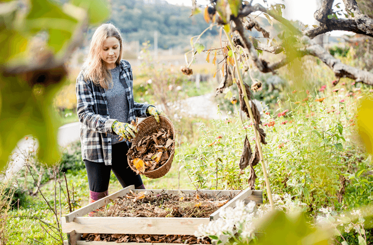Junge Frau schmeißt Laub auf Kompost