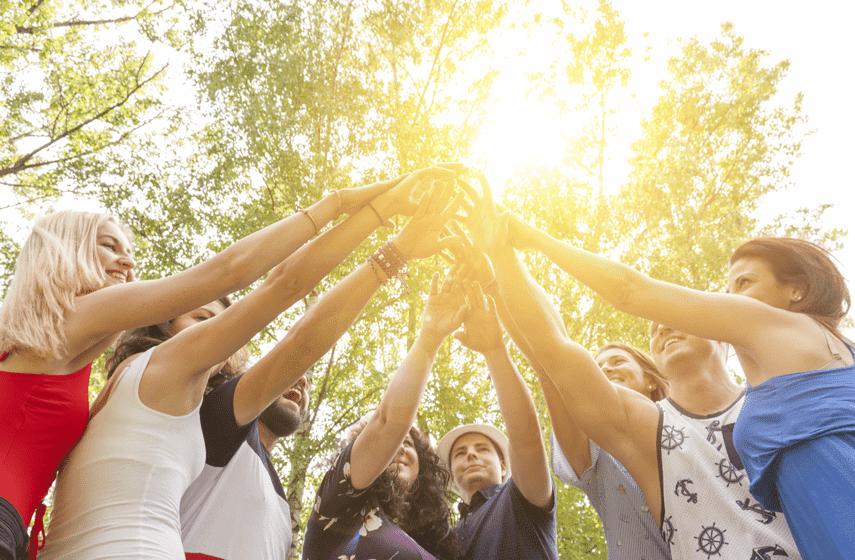 Junge Menschen halten Hände zum Sonnenlicht